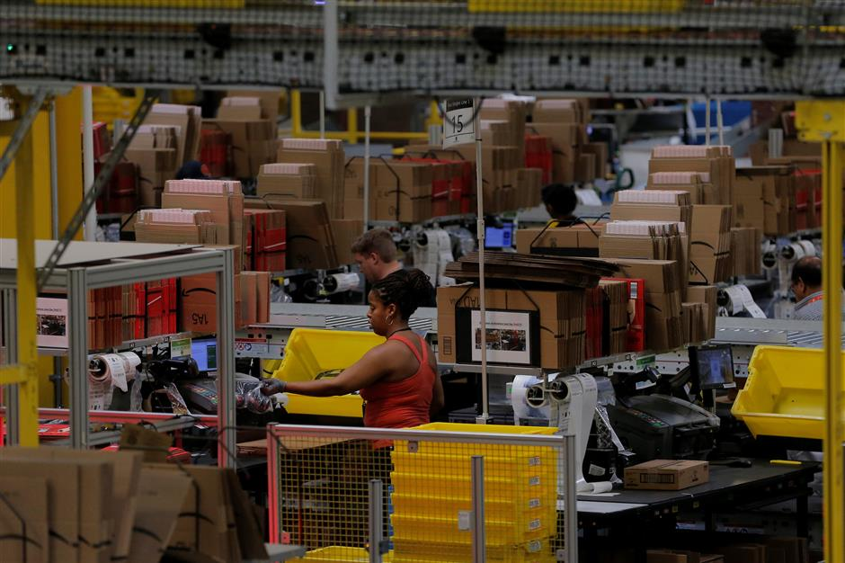 A worker sorts products into a box inside of an Amazon fulfillment center in Robbinsville, New Jersey, U.S., November 27, 2017. REUTERS/Lucas Jackson