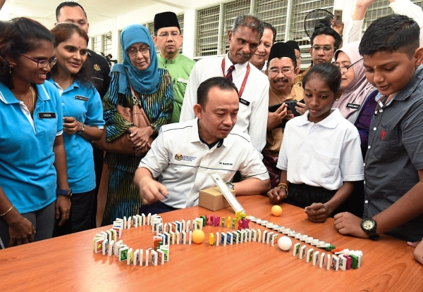 Chain reaction: Maszlee observing a  domino demonstration at SJK(T) Sungai Ara in Bayan Lepas.
