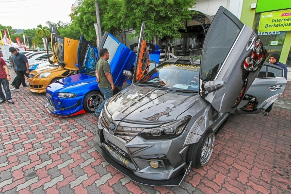 Cars modified with scissor doors on display.