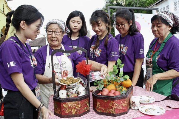 Penang Hainan Association member Tan Chiew Lan (in white apron) showing event volunteers the array of food typically presented during a Mua Gue or a newborn's full moon celebration.