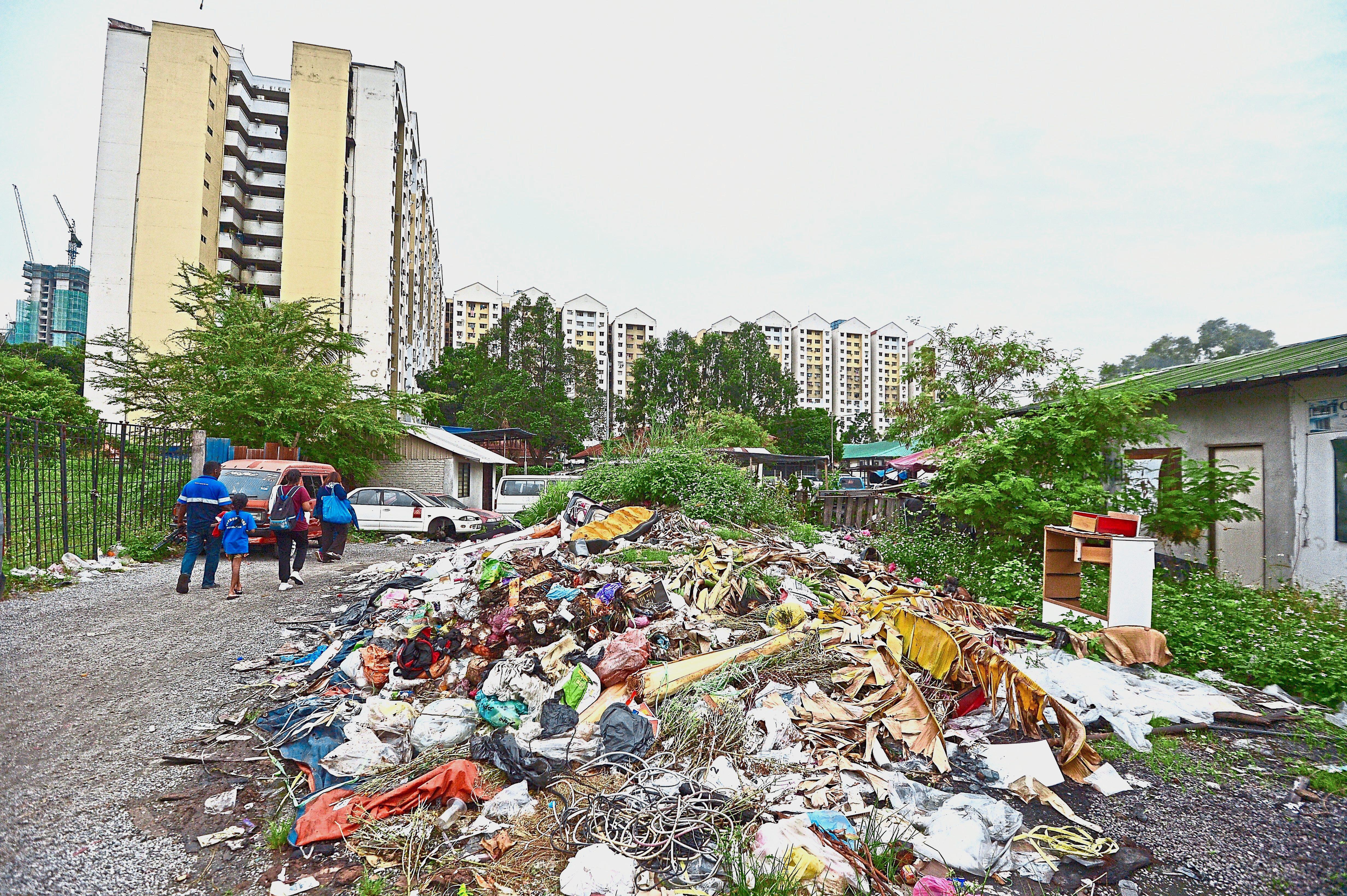 Children have to walk past this heap of trash at a vacant land on their way home to PPR Taman Putra Damai Lembah Subang in Kelana Jaya. — Photos: RAJA FAISAL HISHAN/The Star