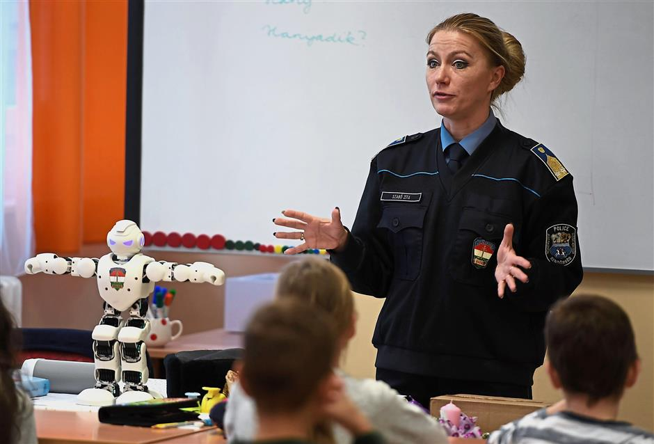 Schoolchildren listen intently to a presentation about Internet security given by local police chief, lieutenant colonel Zita Szabo (R) and Robi in a primary school in Szolnok. - AFP
