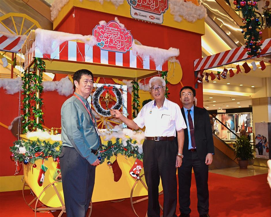Phee (centre) ringing a bell to mark the launch of the Christmas Fun Factory-themed festive celebration at Sunway Carnival Mall in Seberang Jaya. With him are Chow (left) and Woo.