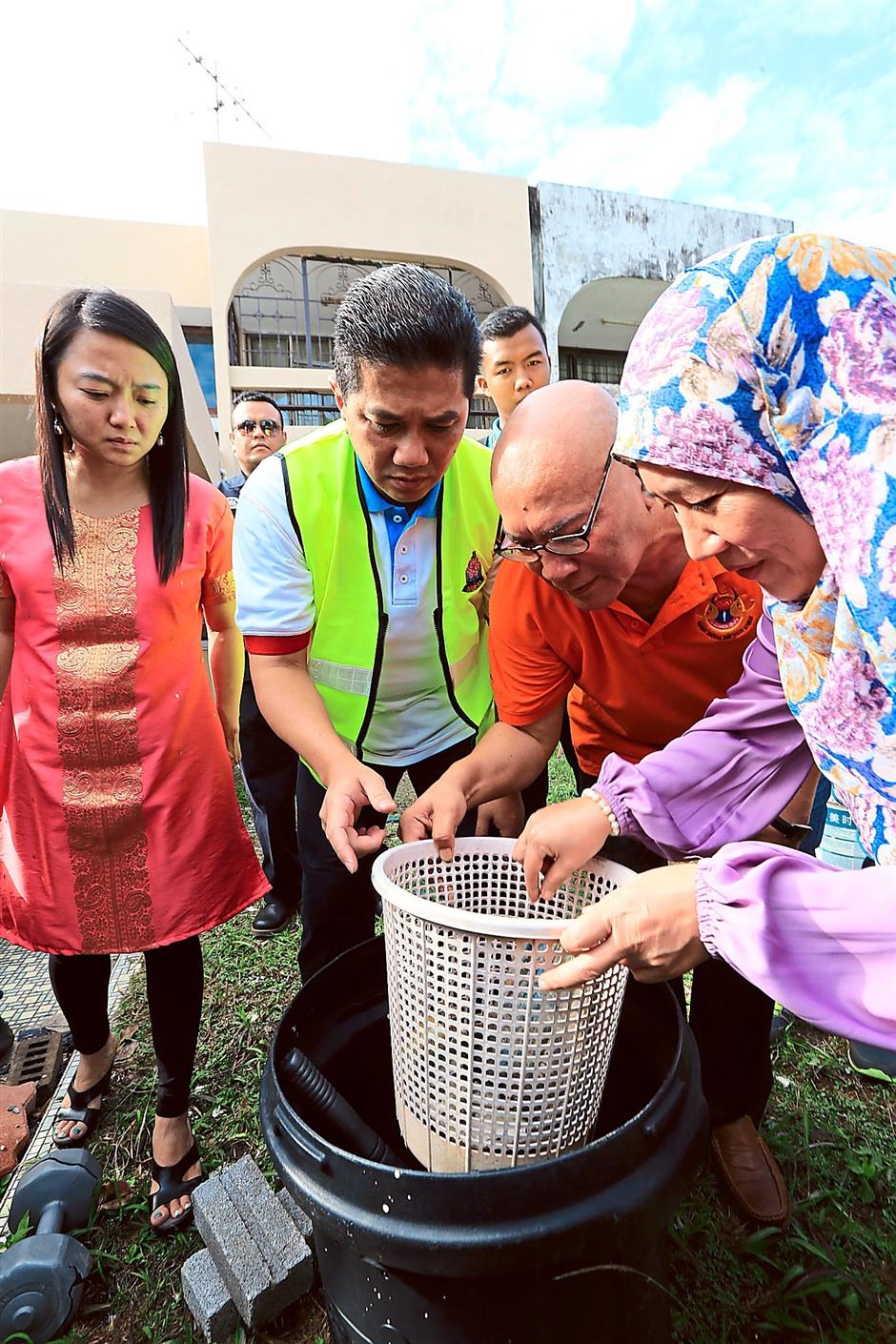 Spot check: Azmin (in vest) checking for mosquito larvae during the event. With him is Yeoh (left), Nor Hisham (third from left) and Dr Daroyah.