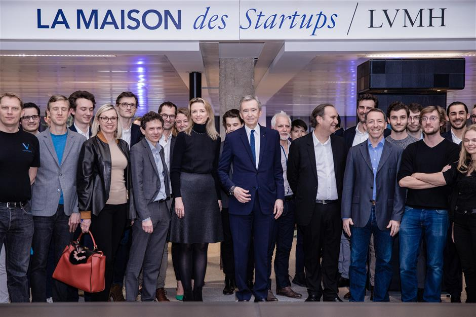 Bernard Arnault, billionaire and chief executive officer of LVMH Moet Hennessy Louis Vuitton SE, center, stands for a photograph during the inauguration of the LVMH start-up accelerator at Station F technology campus in Paris, France, on Monday, April 9, 2018. The accelerator aims to encourage entrepreneurs who are developing new technologies and services for the luxury industry. Photographer: Marlene Awaad/Bloomberg