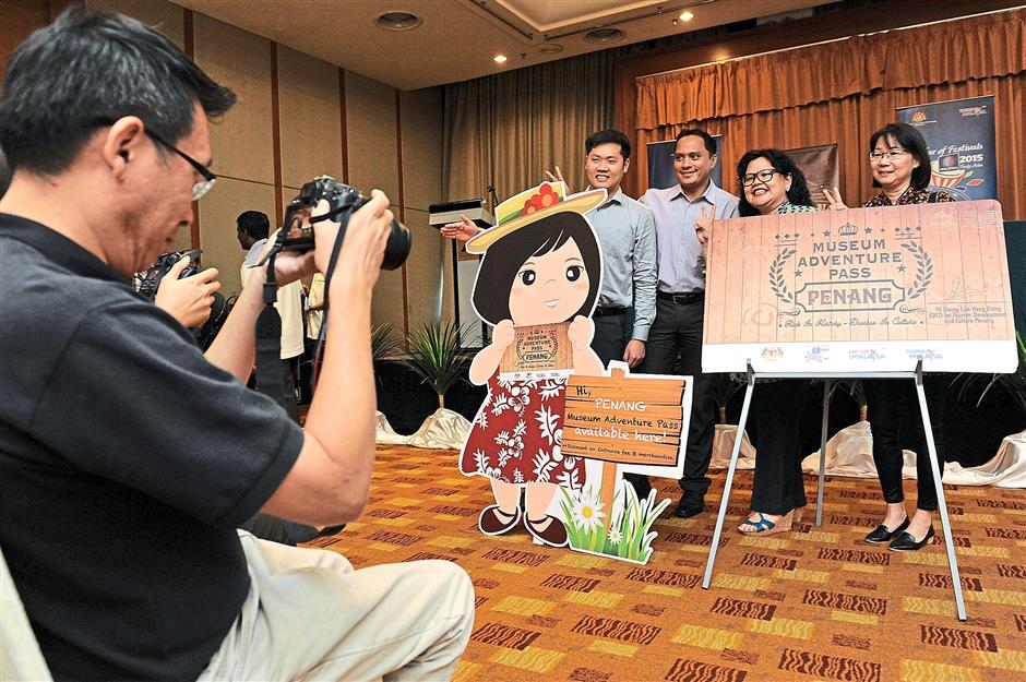 Attractions of Penang: The public posing with a mock museum adventure pass at the launch held at Cititel Hotel, Penang.