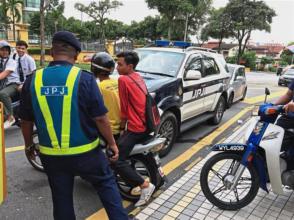 A JPJ enforcement officer reminding students on the need to strictly observe road safety rules and procedures before using their vehicles.