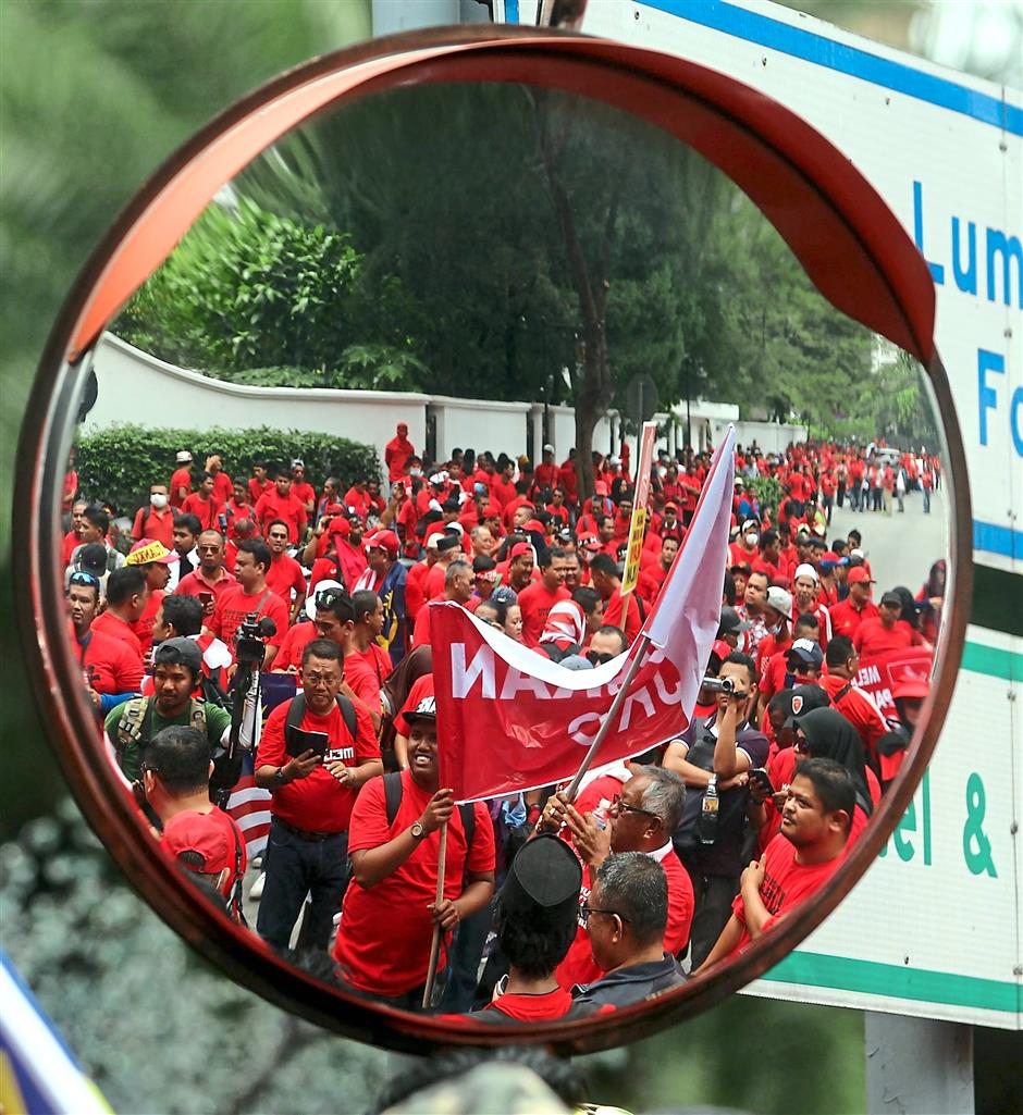 Marching on: Participants of red-shirt rally are seen on a road mirror as they walk along Jalan Raja Chulan.