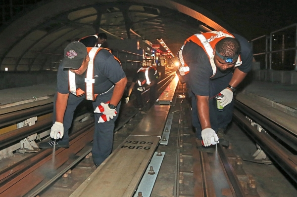 TNMD staff lubricating the rails and track during a re-greasing turn-out process.