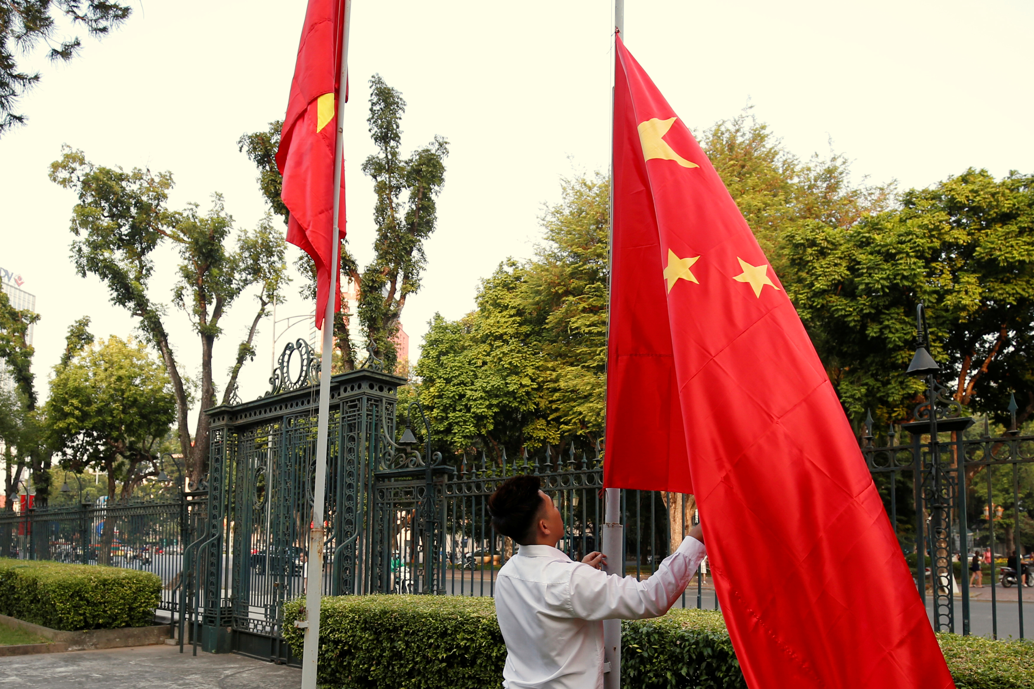 FILE PHOTO: A man raises a Chinese flag (R) next to a Vietnamese flag before a meeting between China's Foreign Minister Wang Yi and Vietnam's Deputy Prime Minister and Foreign Minister Pham Binh Minh at the Government Office in Hanoi, Vietnam November 2, 2017. REUTERS/Kham