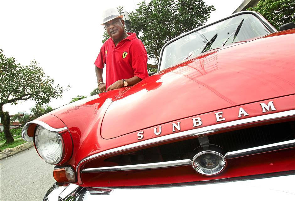 Pride and joy: C. T. Balan posing next to his chilly red Sunbeam Alpine, his weekend car. - AZMAN GHANI / The Star