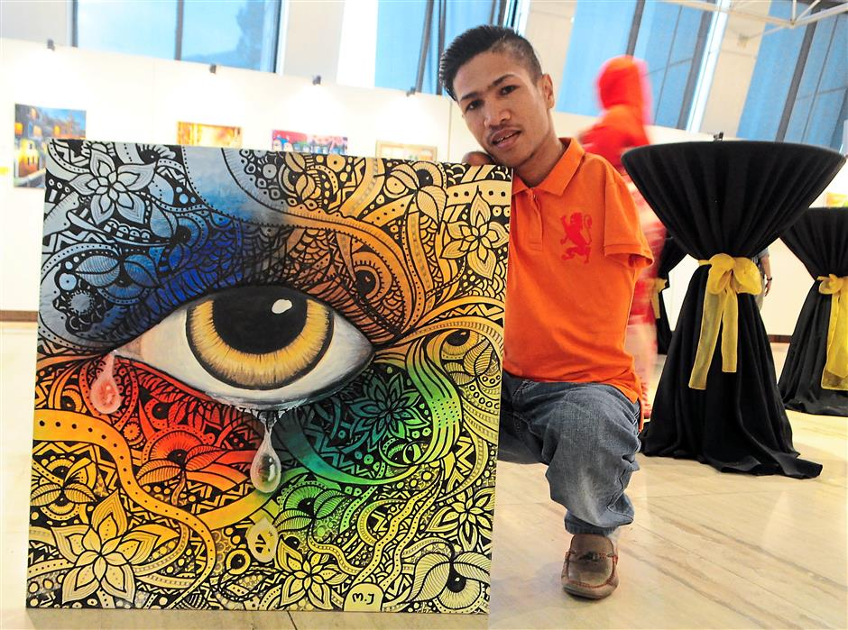 7 Mat Jamil, a foot amd mouth artist poses with an unamed artwork at the show.