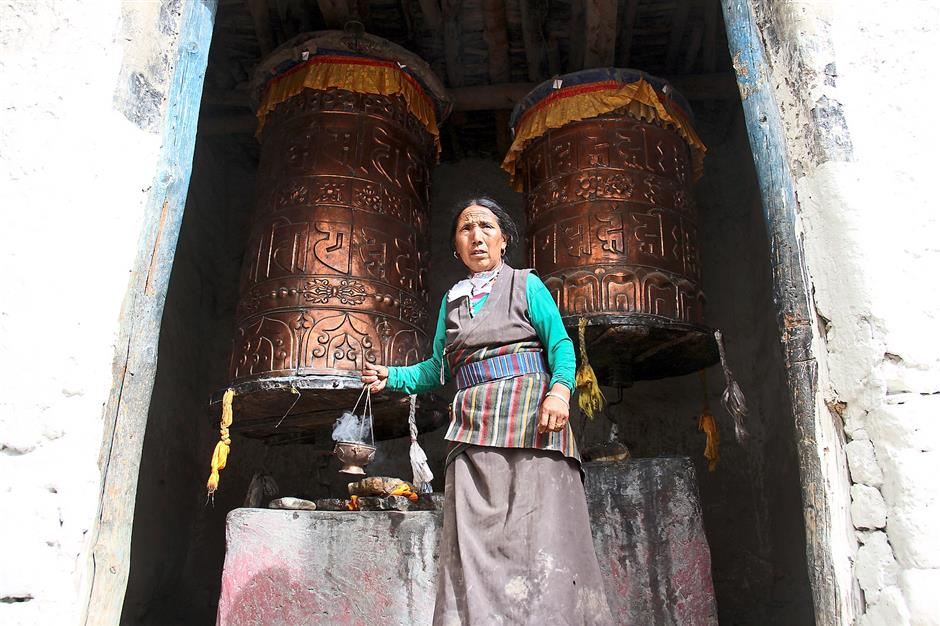 A woman in Lo Manthang with two large Tibetan prayer wheels.