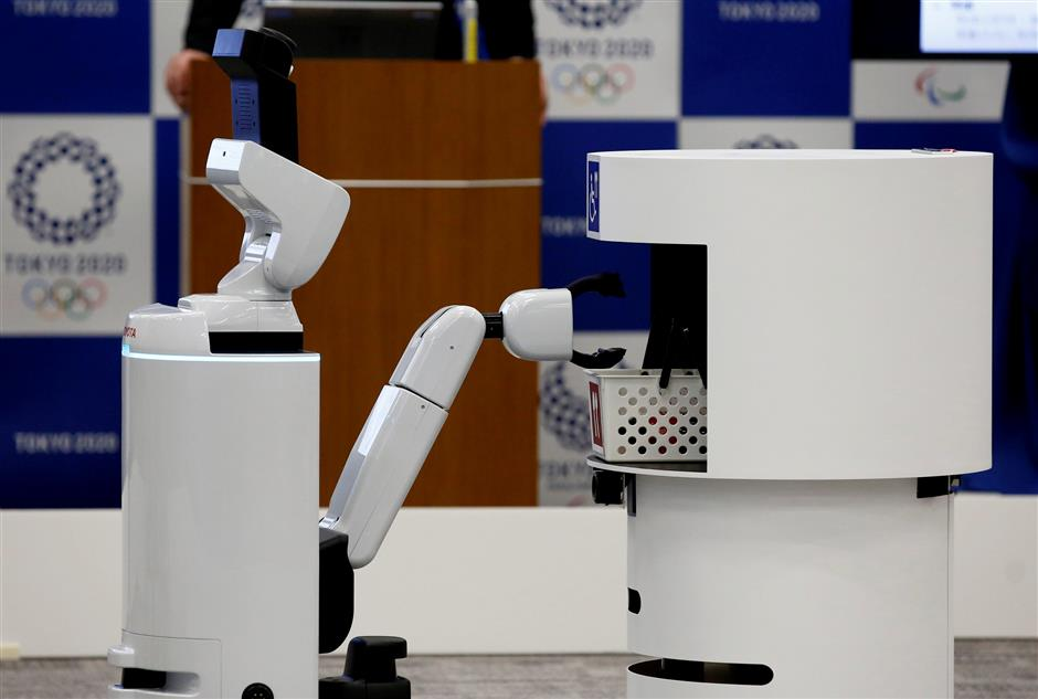 Toyota's HSR (Human Support Robot) (L) picks up a basket from DSR (Delivery Support Robot) at a demonstration of Tokyo 2020 Robot Project for Tokyo 2020 Olympic Games in Tokyo, Japan, March 15, 2019. REUTERS/Kim Kyung-hoon