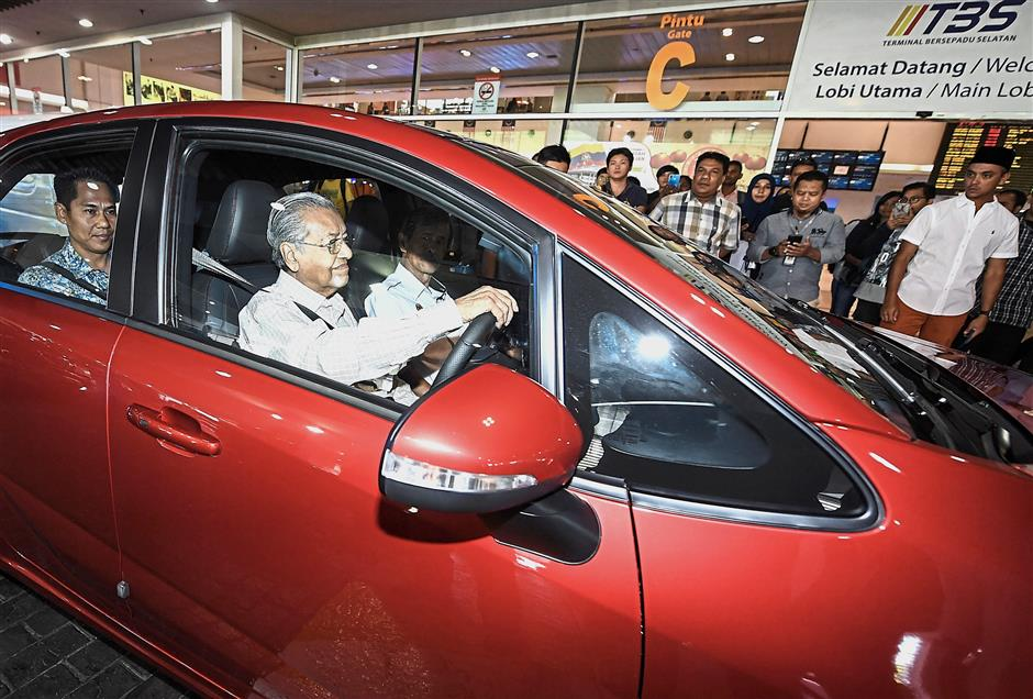 Driving force: Dr Mahathir at the wheel of a Proton Iriz as he makes his way to Terminal Bersepadu Selatan(TBS) in Kuala Lumpur for a visit ahead of Chinese New Year. — Bernama