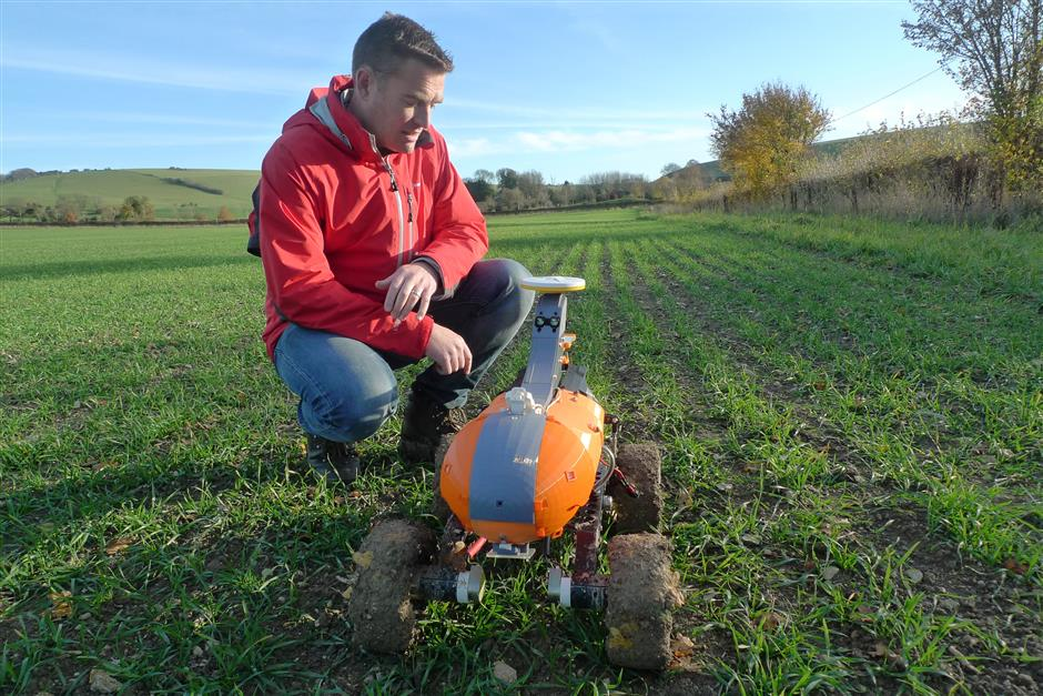 Joe Allnutt, lead roboticist at British startup company the Small Robot Company, inspects a farming robot named Tom as part of a trial in East Meon, southern England, Friday Nov. 30, 2018.  The u201cagri-techu201d startup company is developing lightweight autonomous machines that can carry out precision u201cseeding, feeding and weedingu201d in the hope of transforming food production. (AP Photo / Kelvin Chan)