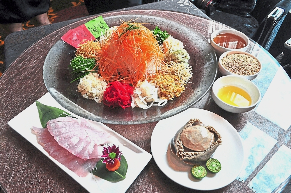 The Grand Imperial RM6,888   menu has yee sang with whole South African abalone and slices of Japanese yellow tail. (Right) Grand Imperial Group business development manager Maggie Chow showing the Alaskan crab that is used to enrich the soup dish for Chinese New Year.