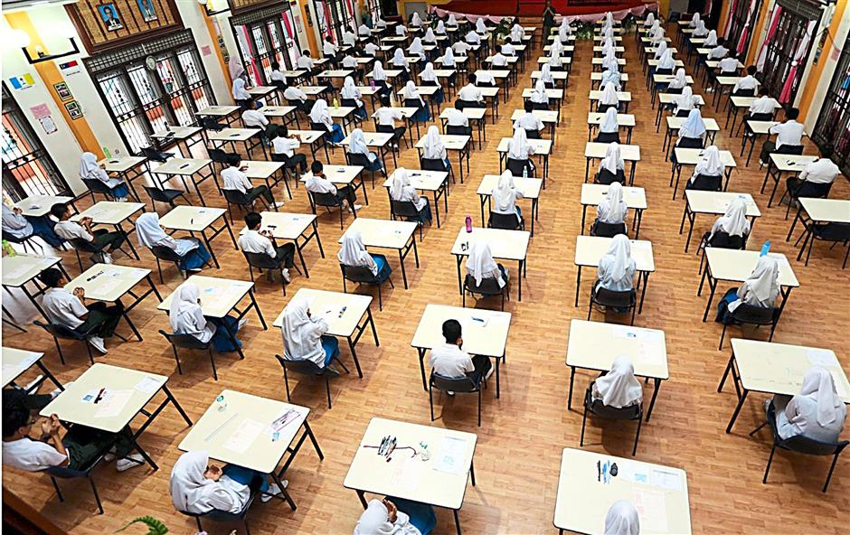 To the old ways? Like the days of the PMR, Form Three students will be sitting for written tests yet again. - File photo