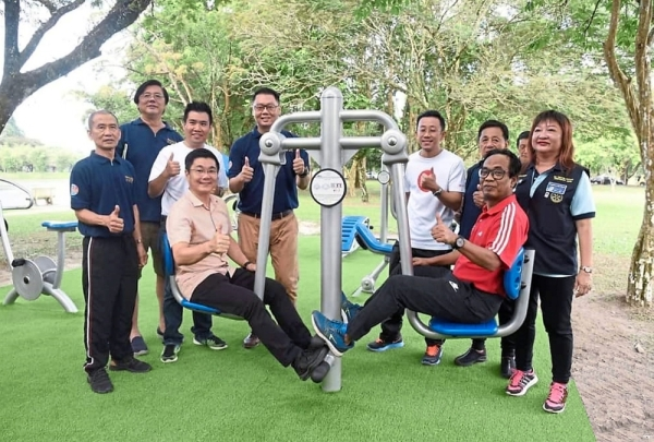 Borhan (seated, right) and Teh (seated, left) trying the new equipment during the launch of the community fitness park at Taiping Lake Gardens.