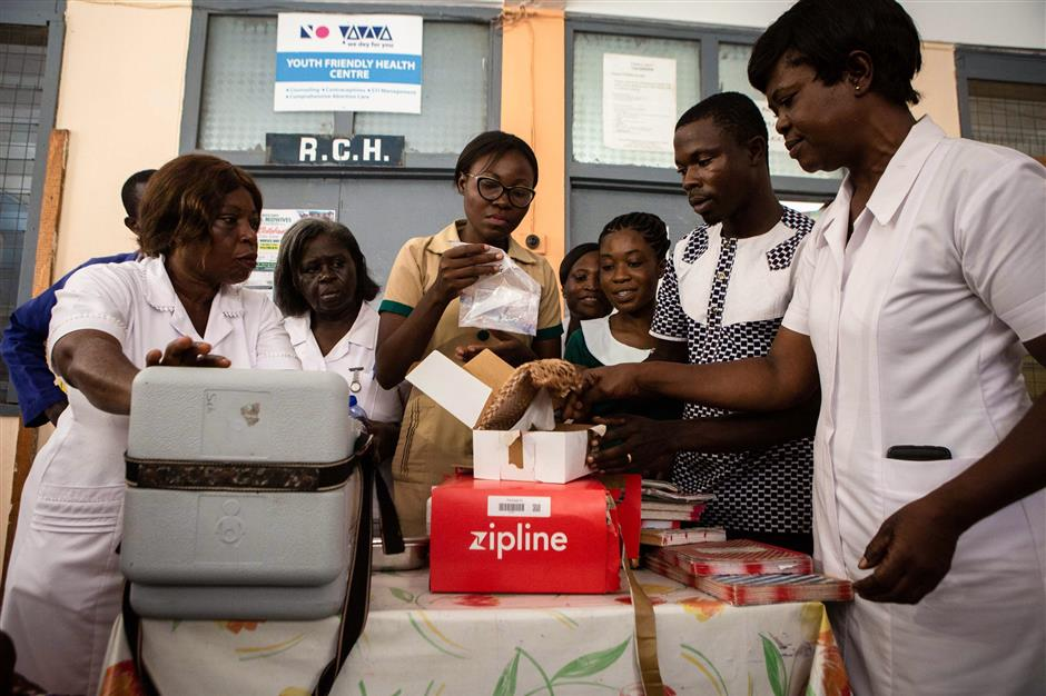 Nurses open boxes with medical supplies delivered by Zipline drones at the New Tafo Government Hospital, in eastern Ghana on April 23, 2019. - Ghana launched a fleet of drones on April 24, 2019 to carry medical supplies to remote areas, with Ghana's President declaring it would become the 'world's largest drone delivery service.' The craft are part of an ambitious plan to leapfrog problems of medical access in a country with poor roads. The drones have been flying test runs with blood and vaccines, but the project was officially inaugurated Wednesday at the main drone base in Omenako, 70 kilometres (40 miles) north of Accra. Operator Zipline, a US-based company, said the three other sites should be up and running by the end of 2019. The drones are planned to ferry 150 different medicines, blood, and vaccines to more than 2,000 clinics serving over 12 million people -- roughly 40 percent of the population. (Photo by Ruth McDowall / AFP)