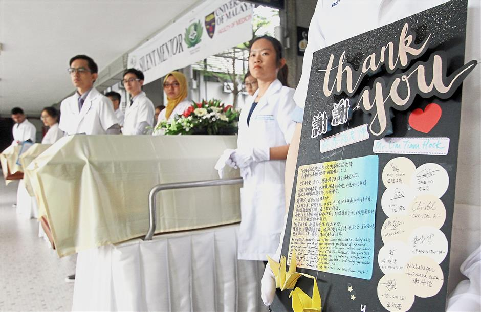 The participants place flowers and thank you cards on the coffins as a sign of gratitude and respect to their mentors.