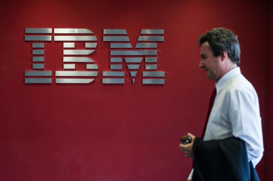 (FILES) In this file photo taken on September 14, 2012, a man passes by a logo at IBM office in Hortolandia, about 100km north from Sao Paulo, Brazil. - IBM said on October 28, 2018 it has reached a deal to buy software company Red Hat for USD 34 billion, a move the computing giant said would enhance its cloud offerings, a key area of growth. (Photo by Yasuyoshi CHIBA / AFP)