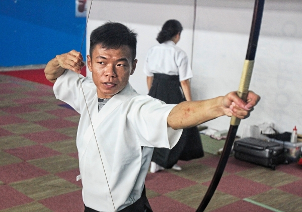 Ng demonstrating the strength of the bowstring.