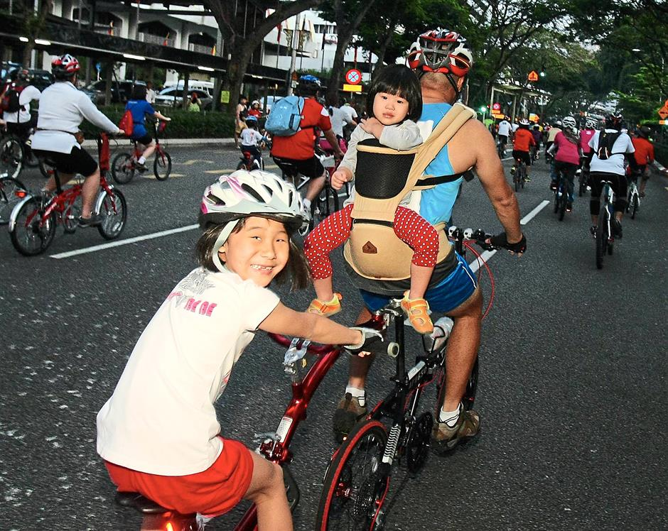 Happy trio: A family having fun on a tandem bicycle during the event.