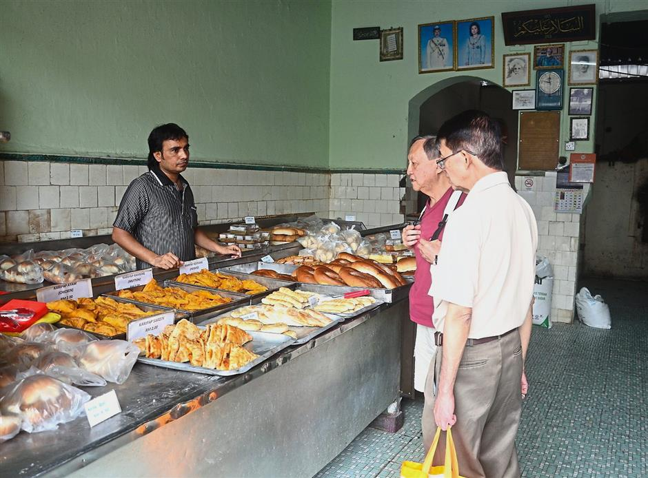 Customers selecting pastry at Salahuddin Bakery in Jalan Dhoby, one of the surviving old-world bakeries in Johor Baru.