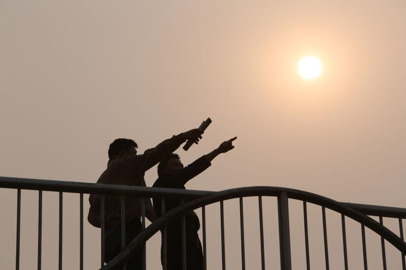 Two residents on a bridge in Beijing. Government economists expect the authorities to up extra spending in combination with reforms to counter the slowdown in China's economy - AFP Photo.