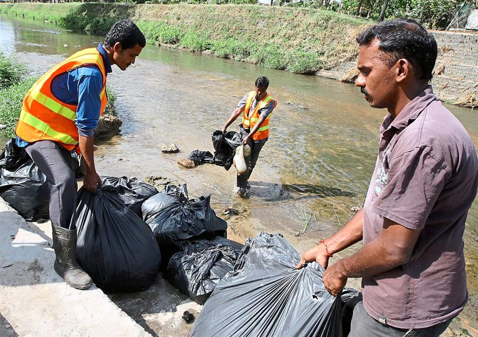 Plenty to collect: Workers clearing up garbage including cut hair by the river next to the KTM Komuter station at Batu Caves after Thaipusam.