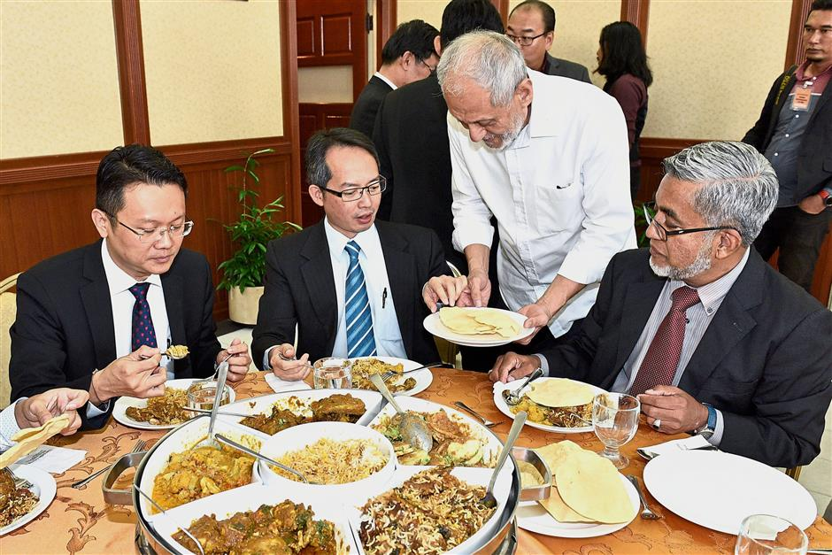 (Above) State elected representatives, government officials and media personnel having a light meal during tea break at the state assembly.(Left, in white) Jamal serving a plate of papadom to Law who is sharing a table with (from right) Yeoh Soon Hin and Datuk Abdul Malik Abul Kassim during lunch.
