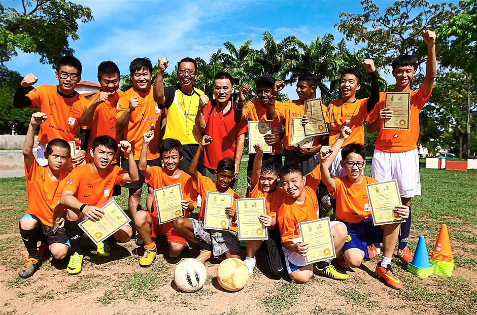 Well done, boys:   The young players showing off the certificates they received from Teh (red T-shirt) after   completing their training.