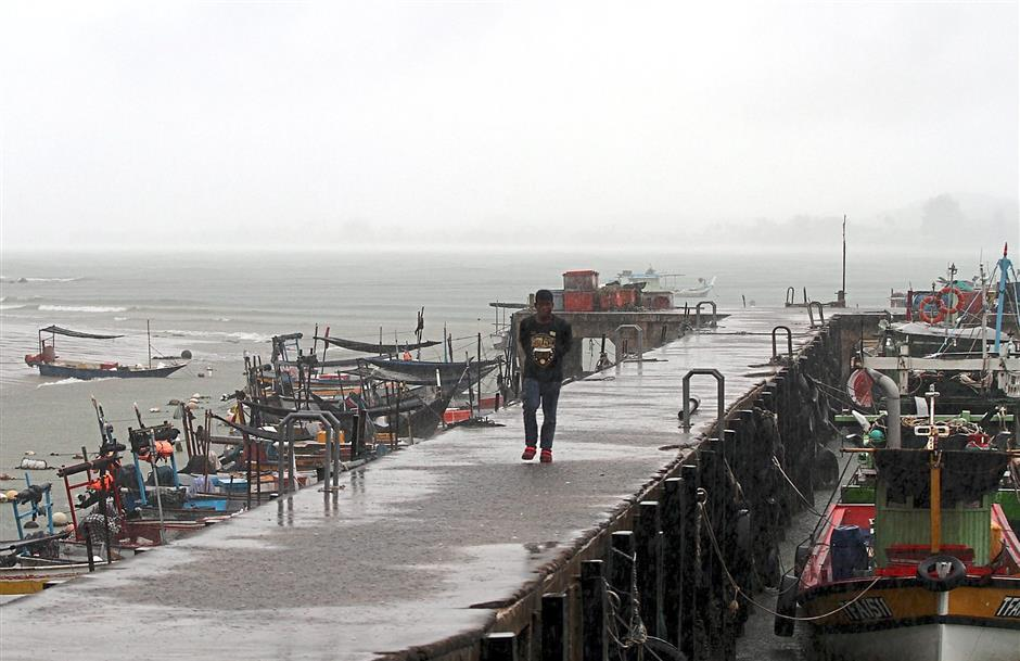 Out of work: A fisherman walking between rows of boats anchored at the fisherman's jetty in Cendering during heavy rain.