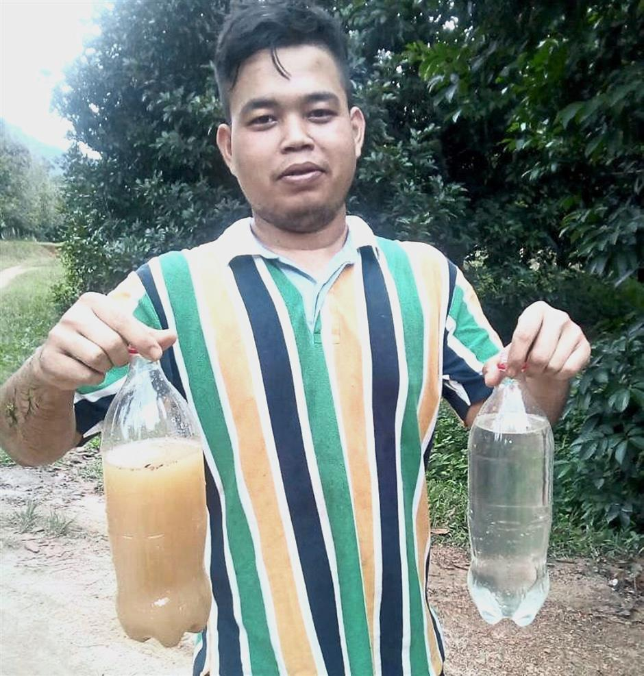 Not safe to drink: A villager with water samples collected showing the 'before' and 'after' effects of the logging activity.