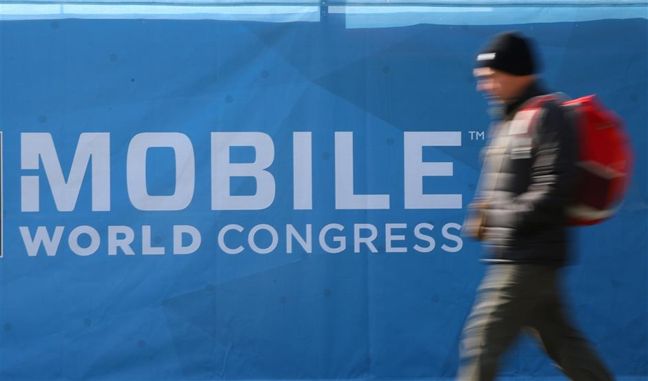 A man walks past a banner of the Mobile World Congress in Barcelona, Spain, February 22, 2018.  REUTERS/Albert Gea