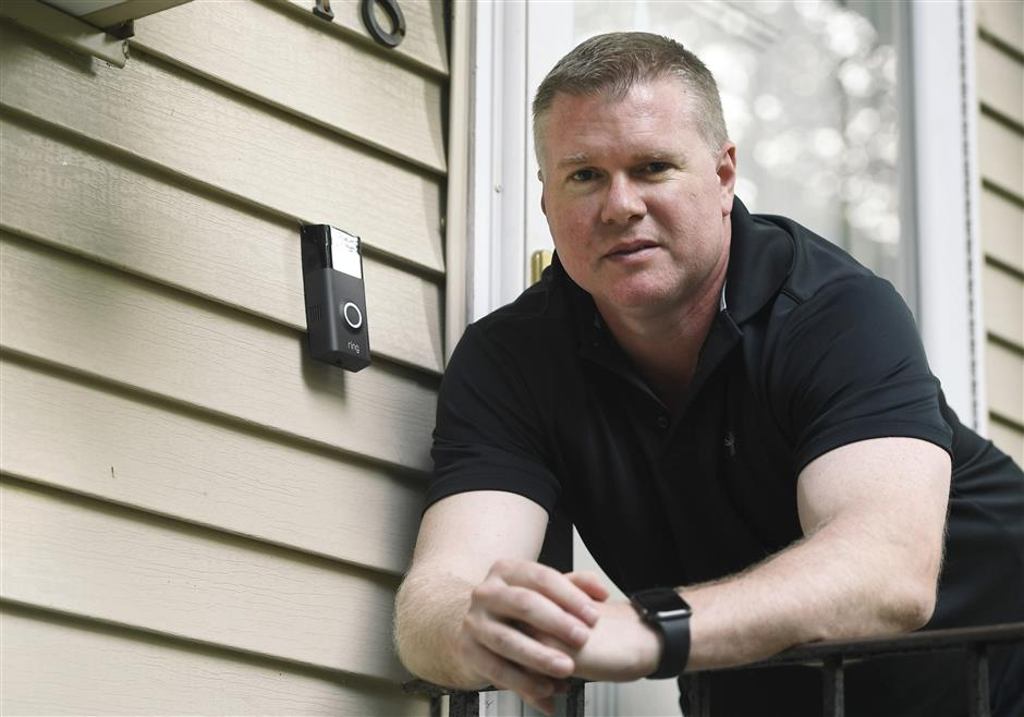 In this Tuesday, July 16, 2019, photo, Ernie Field poses for a photograph next to a Ring doorbell camera at his home in Wolcott, Conn. Field won a free Ring camera and said he had to register for the app to qualify for the raffle. Now he gets alerts on his phone when a car drives by and a 30-second video when his daughter gets home from school. (AP Photo/Jessica Hill)