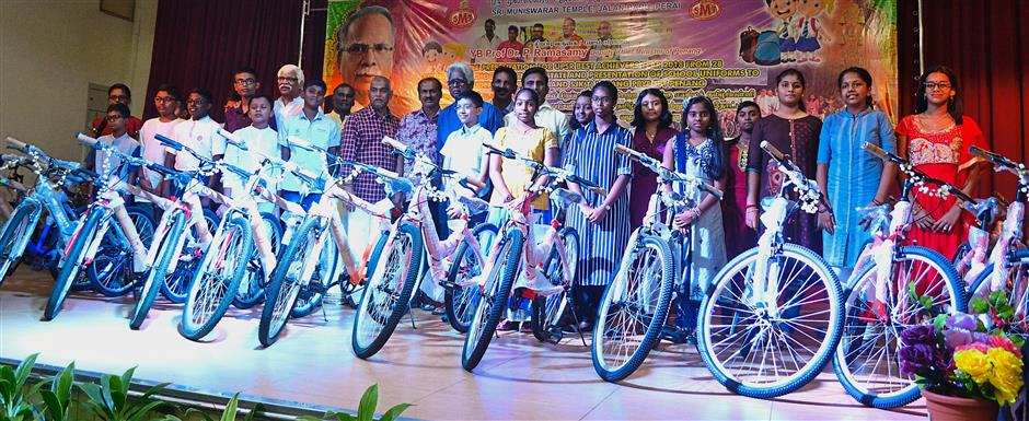 Some of the recipients posing with their bicycles together with Gopalakrishnan (checked shirt), the temple committee and guests at the temple hall.