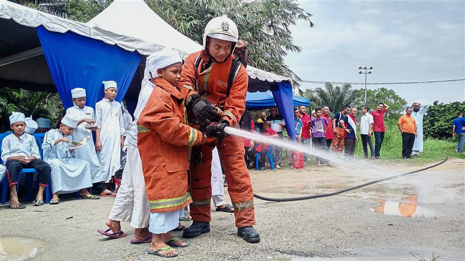 Mohamad Rasyidin had his first experience in putting out a fire assisted by a fireman during a fire safety and rescue demonstration at a tahfiz school.