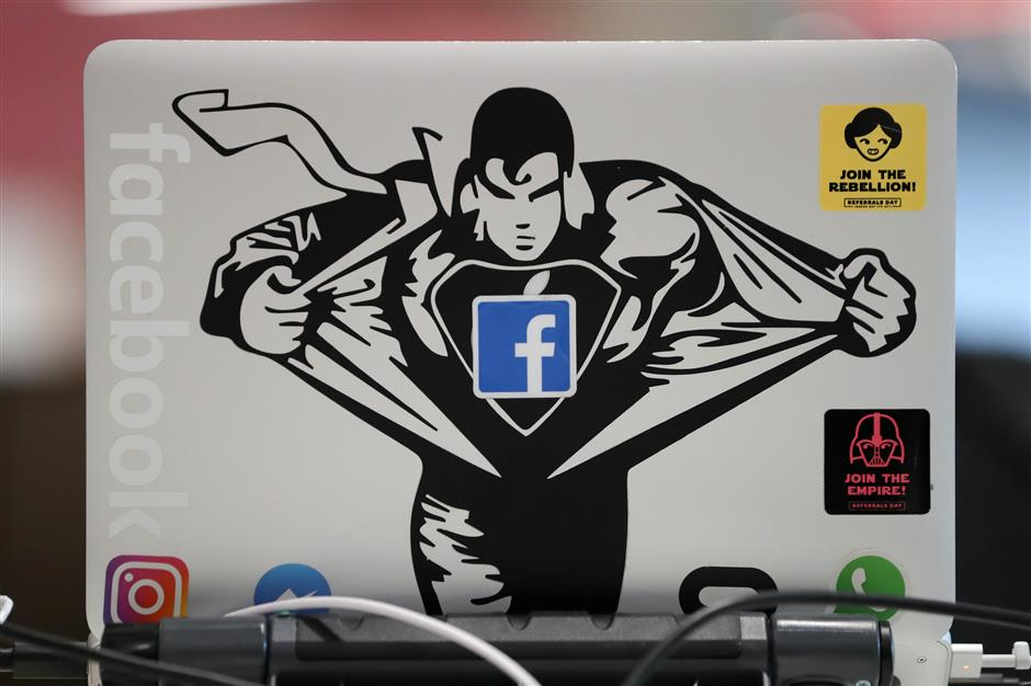 A Facebook sticker is pictured on a laptop at Facebook\'s new headquarters, designed by Canadian-born American architect Frank Gehry, at Rathbone Place in central London on December 4, 2017. Social media titan Facebook opened a new office in London on December 4, 2017, that is set to be its biggest engineering hub outside America, the company has announced. / AFP PHOTO / Daniel LEAL-OLIVAS