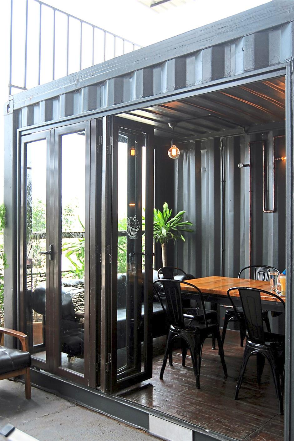 One of the containers is converted into a small meeting room, complete with a folding glass door and some furniture made in-house.