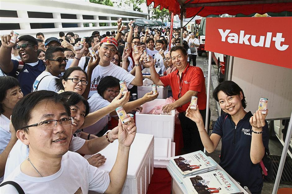 Thirsty participants collecting free drinks from the Yakult booth.
