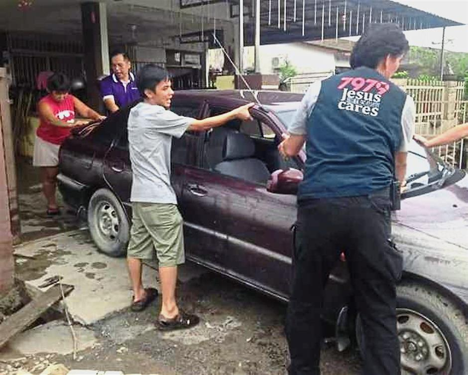 Car trouble: Flood victims moving a car which was inundated by the floodwaters last week.