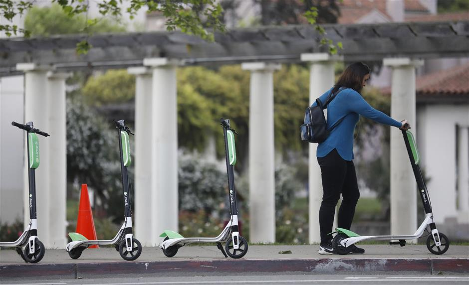 A patron uses her app to unlock a Lime-S electric scooter on Tuesday, April 10, 2018 at Lake Merritt off Grand Avenue in Oakland, Calif. (Laura A. Oda/Bay Area News Group/TNS)