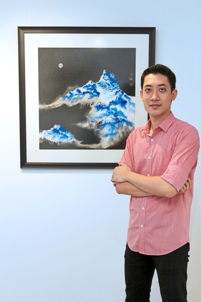Chang with one of his ink paintings, 'Moonlight Snow Mountain'.