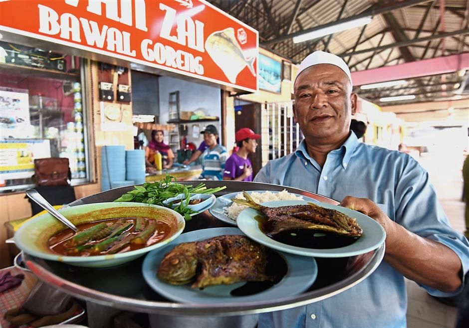 Wan Zainol showing the pomfret and other dishes served at his stall at Astaka Perda Food Court in Bandar Perda.