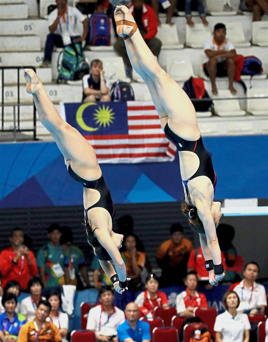 In sync: Leong Mun Yee and Nur Dhabitah Sabri in action for the women's synchronised 10m platform category at the Gelora Bung Karno Aquatic Center last night.