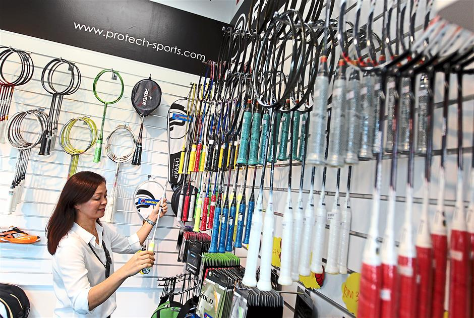 Protech executive director Koh Lee Chin inspecting badminton racquets at the company's outlet at TM Sports Centre in Klang.