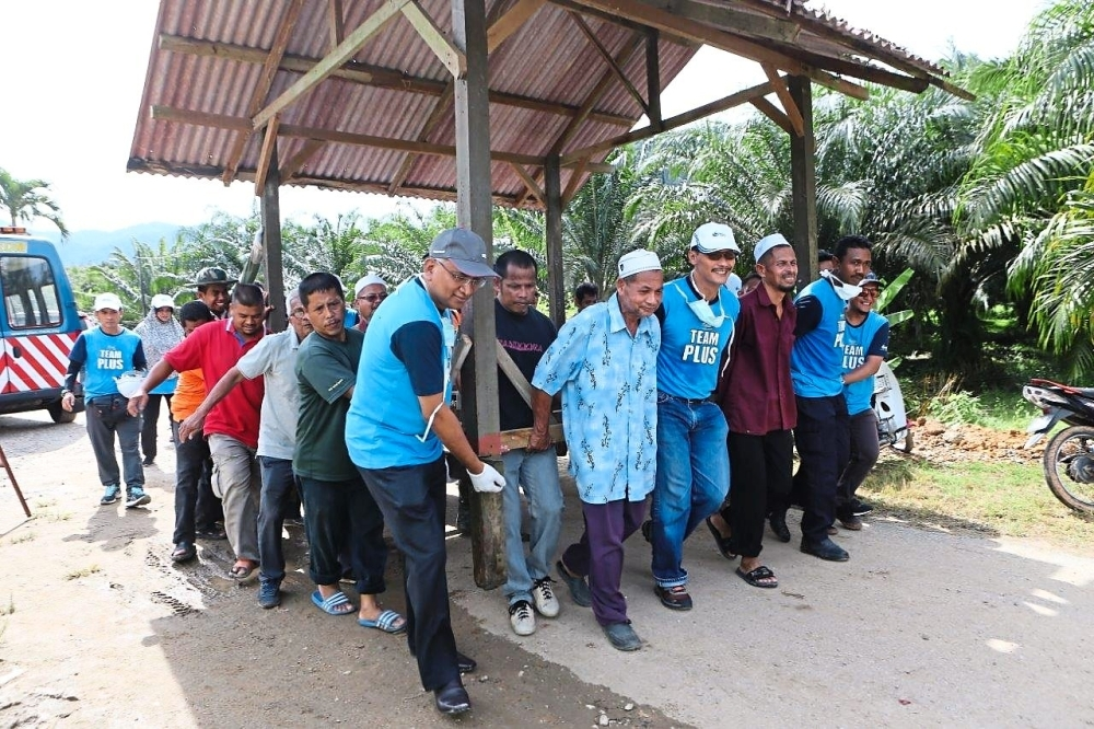 PLUS managing director Datuk Azman Ismail (in grey cap) helping to move a shelter with villagers and volunteers at Kampung Hujung Bandar in Sik, Kedah.