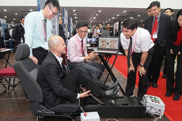 Ong trying out the stroke rehabilitation machine as the winning team members explain how the machine works.
